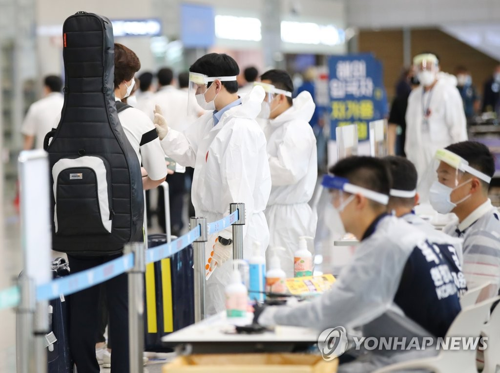 Health officials explain quarantine measures to international arrivals at Incheon International Airport, South Korea's main gateway west of Seoul, on July 1, 2020. (Yonhap)
