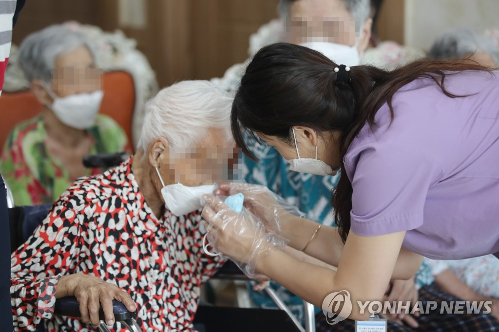 This file photo taken July 7, 2020, shows a worker helping an elderly patient wear a mask at a nursing home in Gwangju, 329 kilometers southwest of Seoul. (Yonhap)
