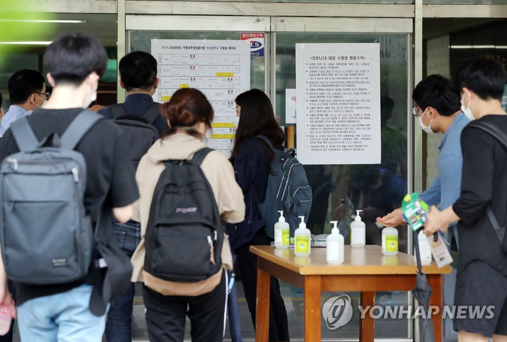 Applicants to take state tests to become public servants disinfect their hands with sanitizer before entering a test venue at a middle school in Gwangju, 329 kilometers southwest of Seoul, on July 11, 2020. (Yonhap)