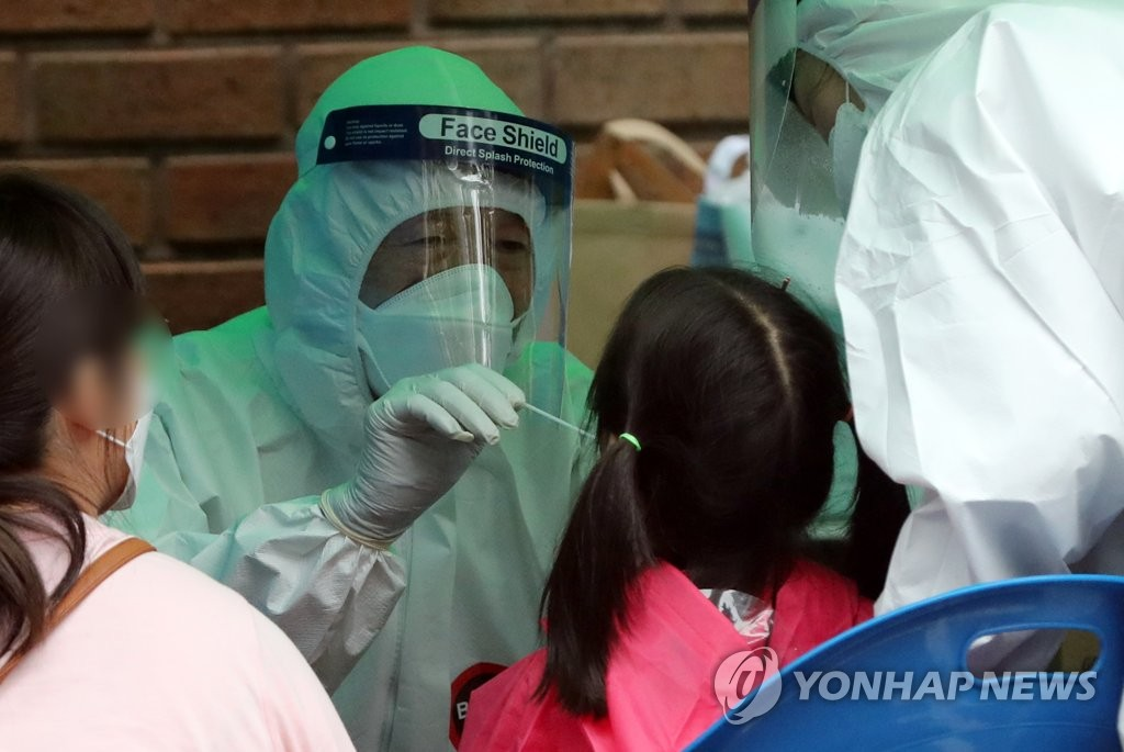 A kindergarten student receives a new coronavirus test at a screening center in Suwon, south of Seoul, on July 13, 2020. (Yonhap)