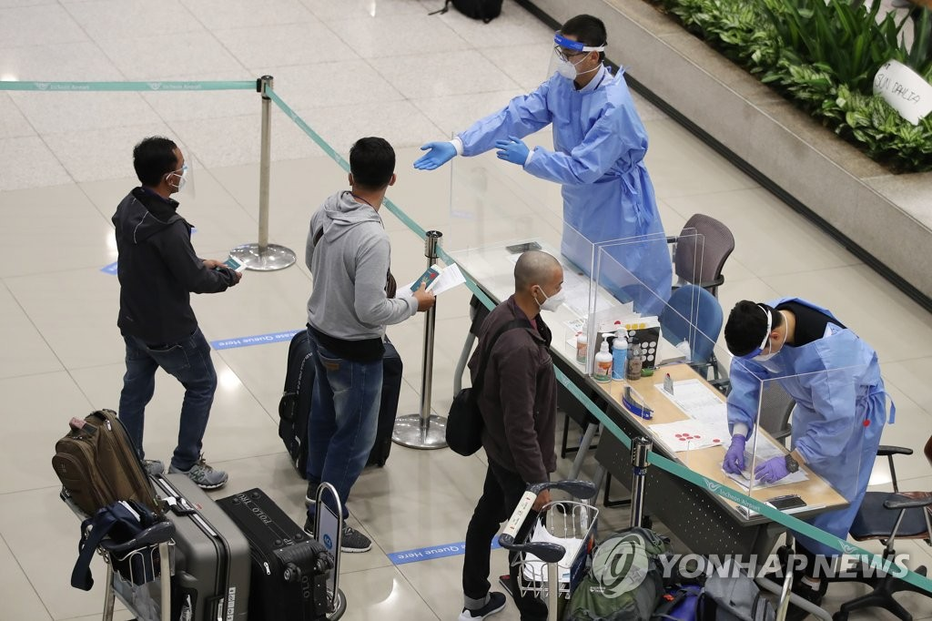 Airport workers check passengers at Incheon International Airport in Incheon, west of Seoul, on July 23, 2020. (Yonhap)