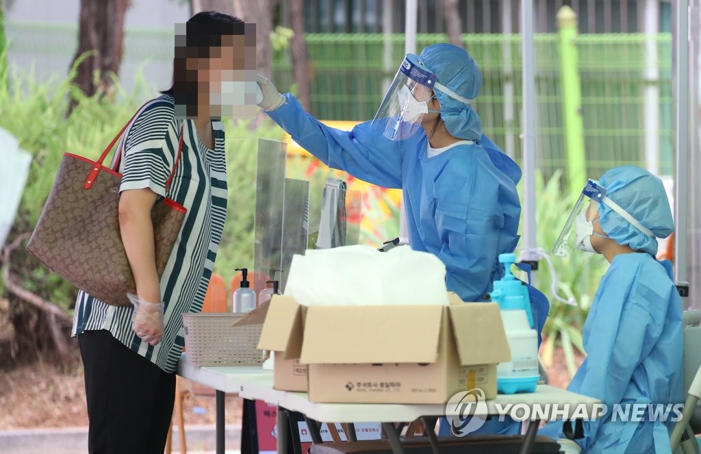 Medical workers carry out a new coronavirus test on a visitor at a makeshift clinic in western Seoul on July 25, 2020. (Yonhap)