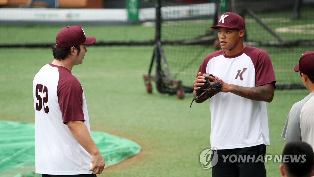 Addison Russell of the Kiwoom Heroes (R) speaks with his teammate Park Byung-ho during practice ahead of a Korea Baseball Organization regular season game against the Doosan Bears at Jamsil Baseball Stadium in Seoul on July 28, 2020. (Yonhap)