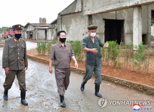 N.K.'s No. 2 man inspects construction of chicken farm