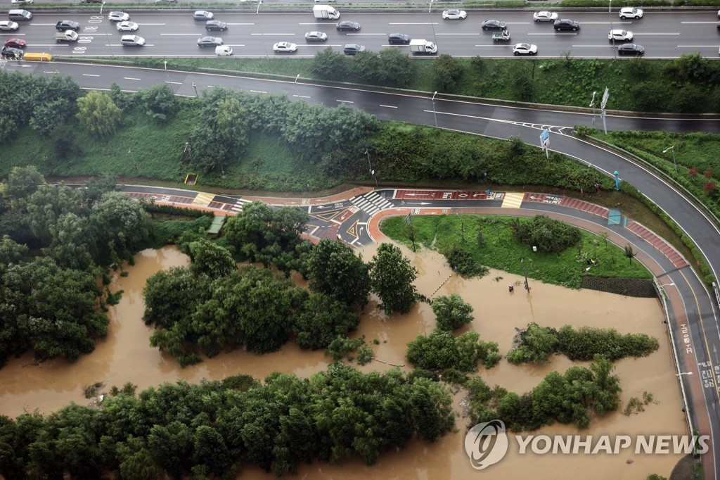 Parts of a road and a riverside park next to Olympic Expressway in southern Seoul are swamped due to heavy rain on Aug. 3, 2020. (Yonhap)