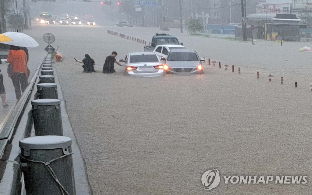 Passengers leave their cars after heavy rain swamped areas of Cheonan, South Chungcheong Province on Aug. 3, 2020. (Yonhap)