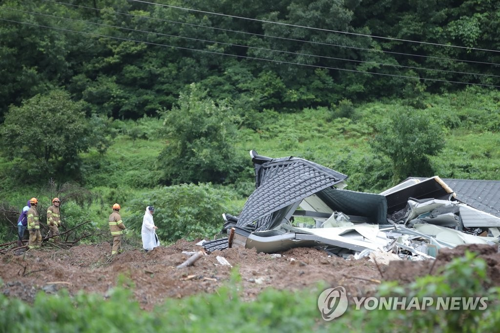 Rescue workers search for a person trapped in the debris of a landslide at a village in Gokseong, about 400 kilometers south of Seoul, on Aug. 8, 2020. Four people were dead and one missing after the landslide triggered by heavy rain. (Yonhap)