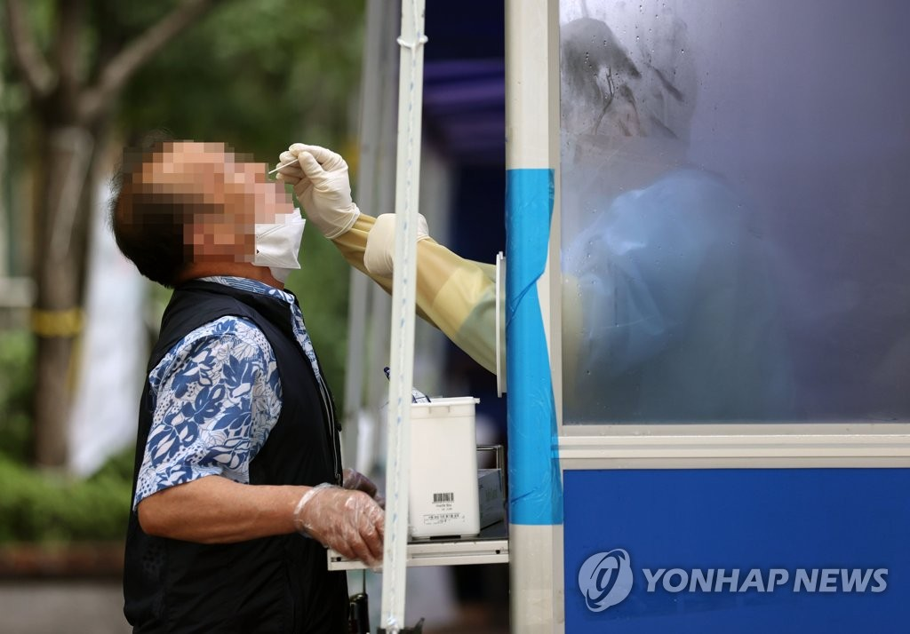 A citizen is tested for the new coronavirus at a screening center installed in central Seoul on Aug. 14, 2020. (Yonhap)