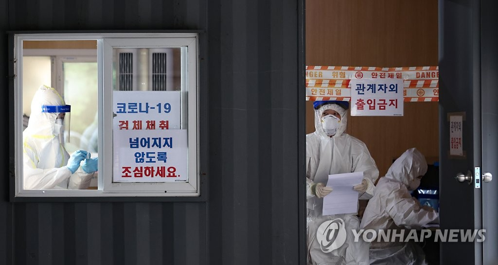 Health workers clad in protective gear prepare to work at a virus screening clinic in Seoul on Aug. 31, 2020. (Yonhap)