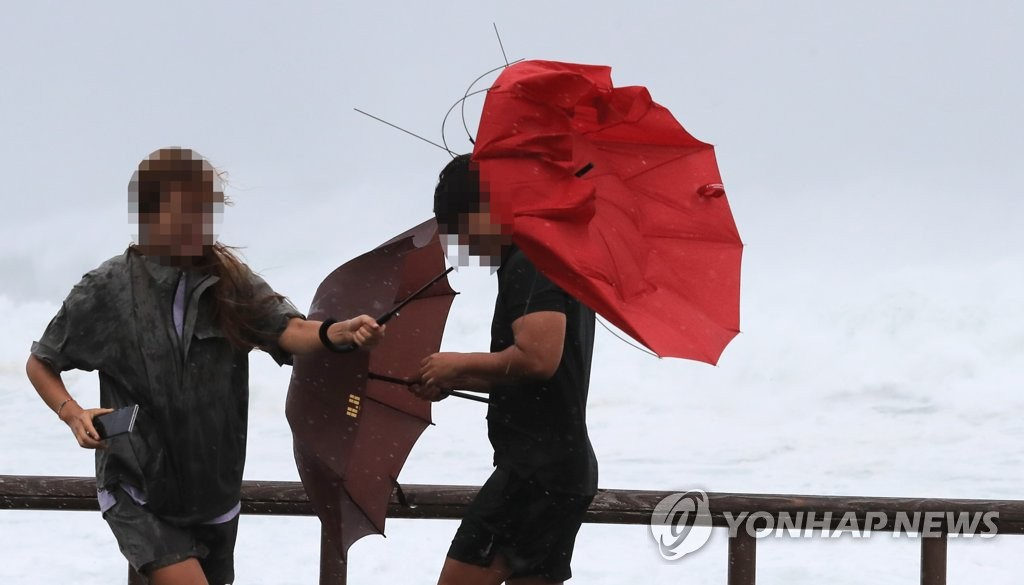 Pedestrians struggle to hold onto their umbrellas at Seogwipo in Jeju on Sept. 2, 2020. (Yonhap)
