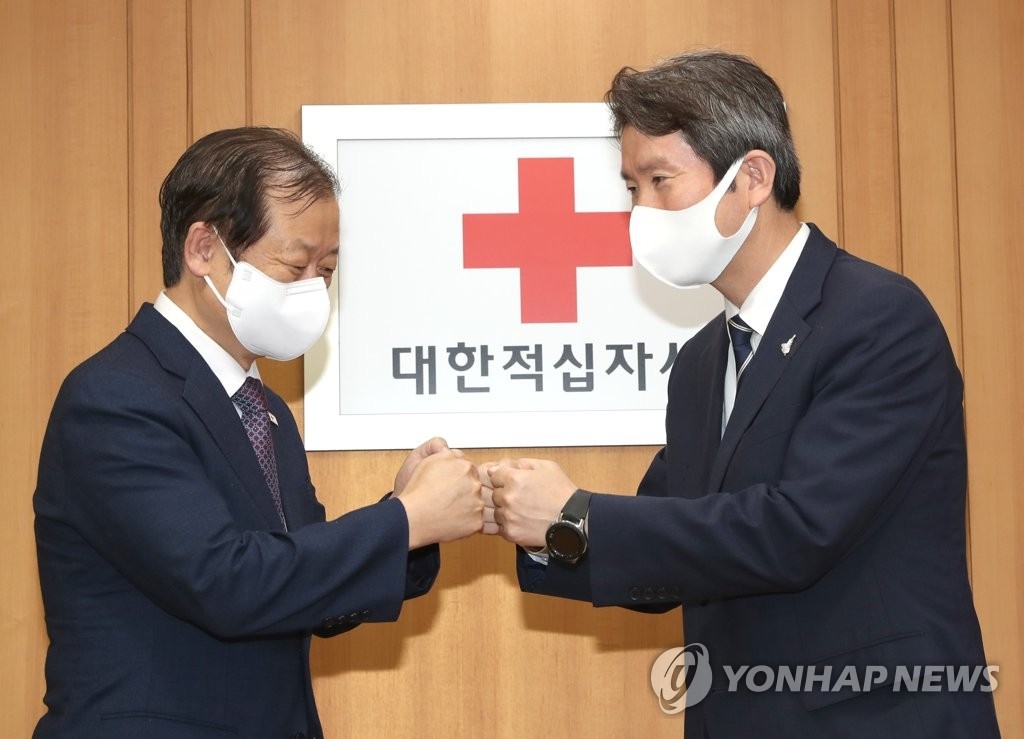 Unification Minister Lee In-young (R) poses for a photo with Shin Hee-yong, chief of Red Cross, during their meeting at the Red Cross building in Seoul on Sept. 2, 2020. (Yonhap)