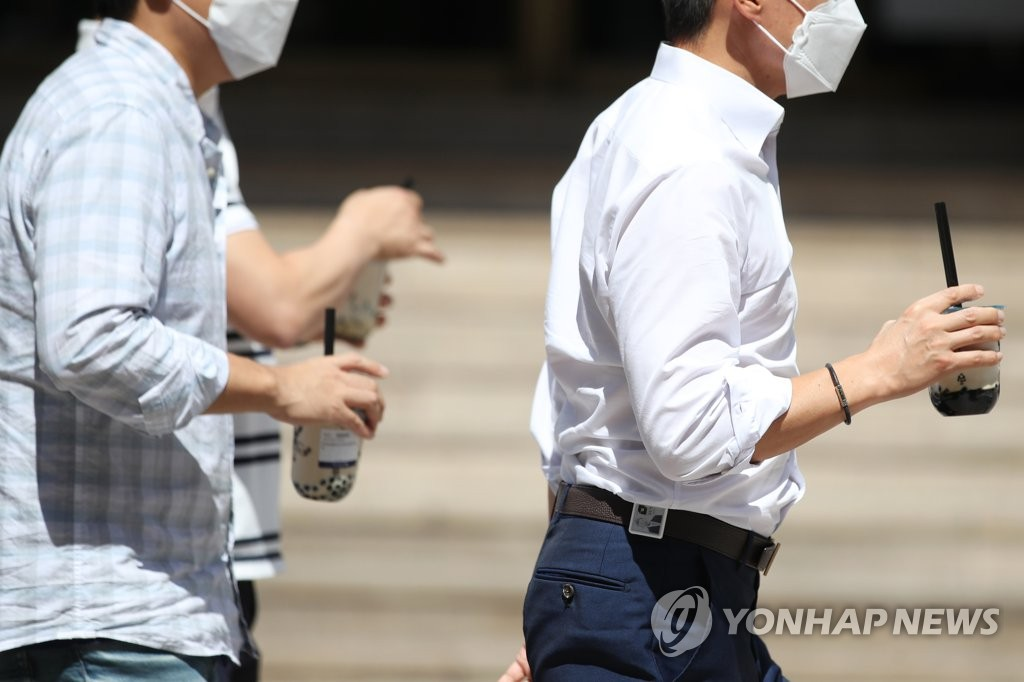 People walk while holding takeout coffee on a street in Seoul on Sept. 4, 2020, as the government decided to extend the toughened social distancing guidelines for the greater Seoul area until Sept. 13. (Yonhap)
