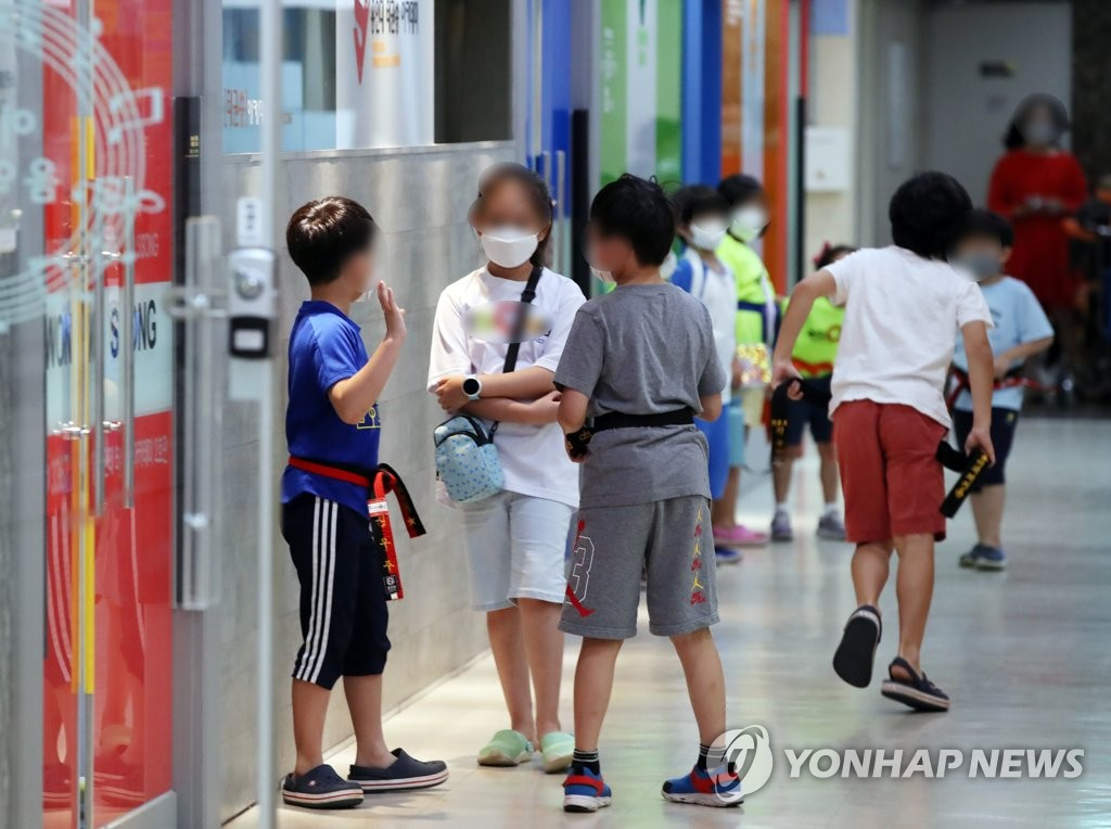 Children chat in front of a reopened private education institute in Seoul on Sept. 14, 2020, the first day of the easing of toughened social distancing guidelines, as new COVID-19 cases noticeably declined. Such private institutions were shut down over the previous two weeks amid a resurgence of the virus. (Yonhap)