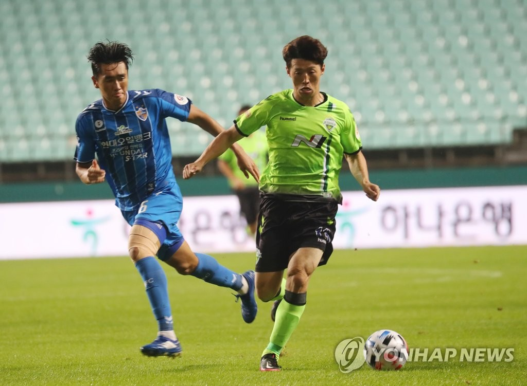 Kim Bo-kyung of Jeonbuk Hyundai Motors (R) dribbles the ball past Won Du-jae of Ulsan Hyundai FC during a K League 1 match at Jeonju World Cup Stadium in Jeonju, 240 kilometers south of Seoul, on Sept. 15, 2020. (Yonhap)