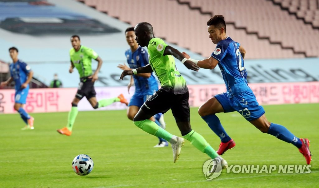 Mo Barrow of Jeonbuk Hyundai Motors (L) dribbles the ball against Ulsan Hyundai FC in a K League 1 match at Jeonju World Cup Stadium in Jeonju, 240 kilometers south of Seoul, on Sept. 15, 2020. (Yonhap)