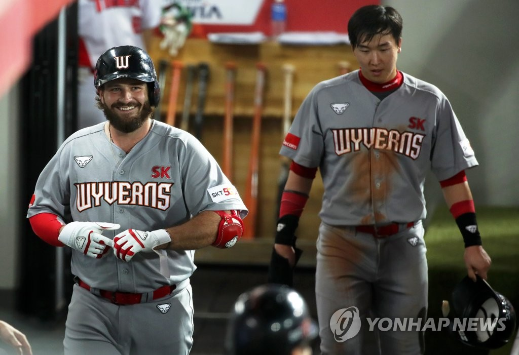 Tyler White of the SK Wyverns (L) smiles in the dugout after hitting a three-run home run against the Kia Tigers in a Korea Baseball Organization regular season game at Gwangju-Kia Champions Field in Gwangju, 330 kilometers south of Seoul. (Yonhap)