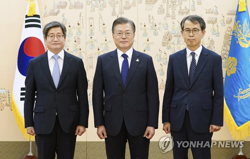 President Moon Jae-in (C) poses for a commemorative photo with New Supreme Court Justice Lee Heung-ku (R) and Kim Myeong-soo, its chief justice, at Cheong Wa Dae in Seoul on Sept. 18, 2020. (Yonhap)