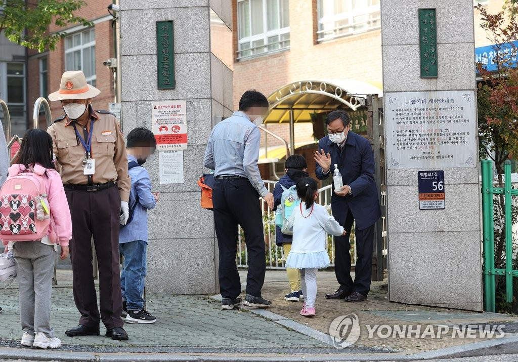Students have their temperatures checked before entering an elementary school in western Seoul on Oct. 12, 2020. (Yonhap)