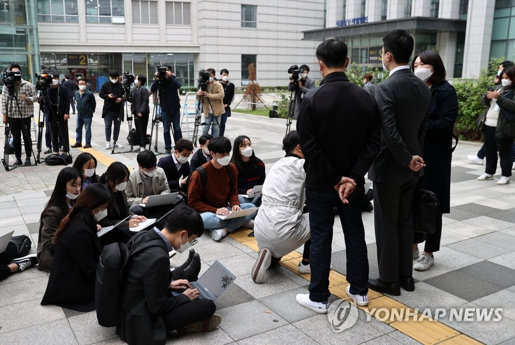 The bereaved family of a patient who died in a case in which a taxi driver blocked an ambulance from heading to a hospital, along with the family's attorney, answers reporters' questions outside the Seoul Eastern District Court in Songpa Ward of Seoul on Oct. 21, 2020. (Yonhap)