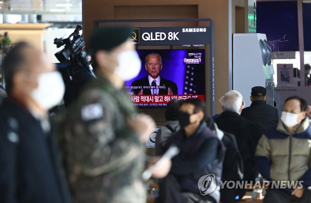 Citizens wearing protective masks watch U.S. President-elect Joe Biden delivering a speech on a TV at Seoul Station in the capital city on Nov. 8, 2020. (Yonhap)