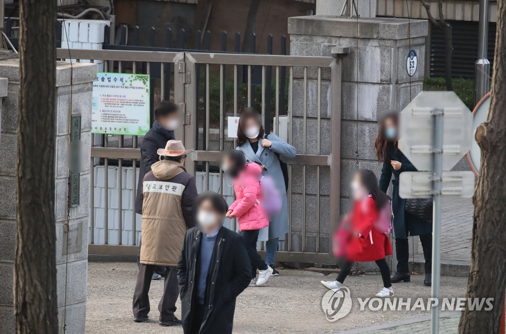 Students go to an elementary school in Seoul on Nov. 24, 2020, on the first day of Level 2 social distancing as part of antivirus efforts. (Yonhap)