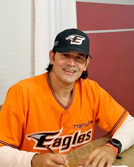 In this Nov. 27, 2020, file photo provided by the Hanwha Eagles, Carlos Subero, new manager for the Korea Baseball Organization club, signs his contract in an undisclosed location in the United States. (PHOTO NOT FOR SALE) (Yonhap)