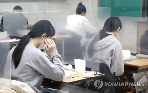 More than 426,000 take college entrance exam as virus surges
