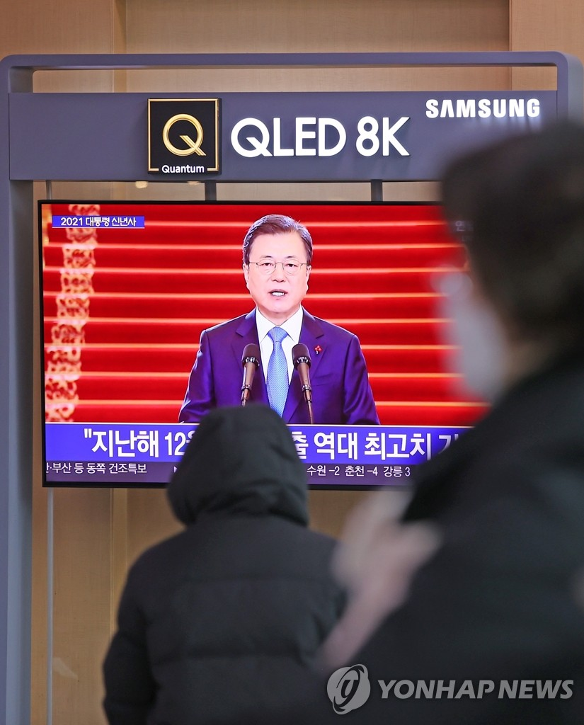 People watch a TV report of President Moon Jae-in delivering a New Year's address at Seoul Station on Jan. 11, 2021. In the televised address, Moon said the government will provide all South Koreans with free-of-charge COVID-19 vaccines in phases starting next month. (Yonhap)