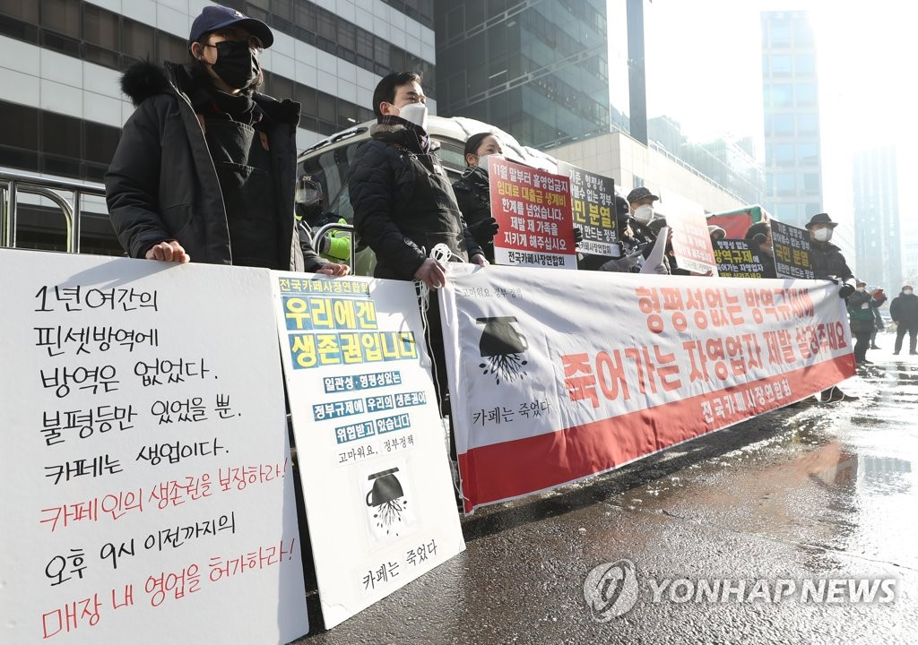 Member of a cafe owners' association demand the lifting of COVID-19 business restrictions during a rally outside the ruling Democratic Party's headquarters in Seoul on Jan. 13, 2021. (Yonhap)