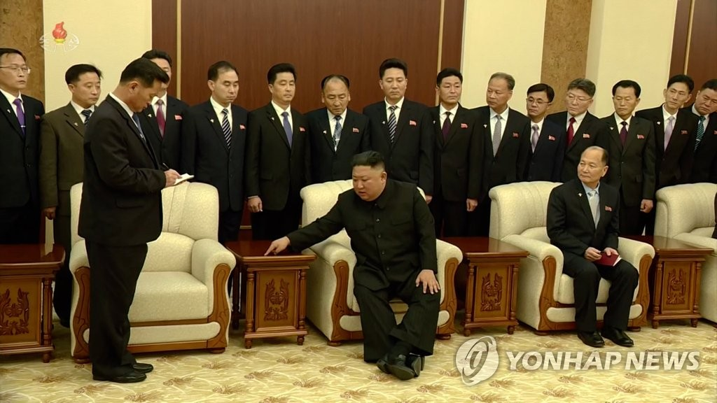 North Korean leader Kim Jong-un (C, 1st row) places his finger on a table as he joins a group photo session with Premier Kim Tok-hun and other newly appointed members of the Cabinet in Pyongyang on Jan. 18, 2021, in this photo captured from the North's Korean Central Television the next day. (For Use Only in the Republic of Korea. No Redistribution) (Yonhap)