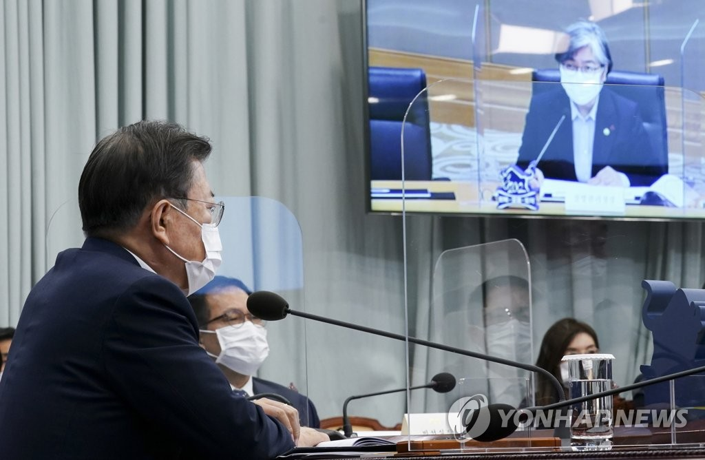 President Moon Jae-in (L) receives a policy briefing from Jeong Eun-kyeong (on screen), commissioner of the Korea Disease Control and Prevention Agency (KDCA), at Cheong Wa Dae in Seoul on Jan. 25, 2021. (Yonhap)
