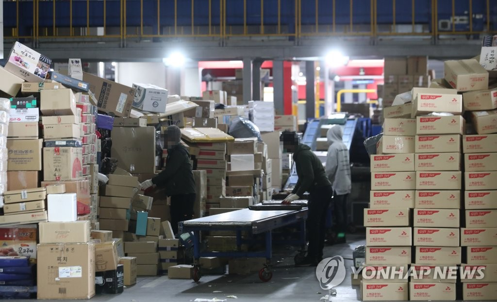 This Jan. 31, 2021, photo shows workers sorting parcels at a logistics center in southeastern Seoul. (Yonhap)