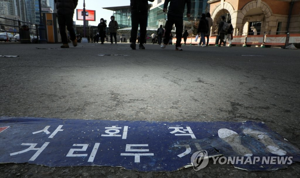 A social distancing sign is posted on the street in front of a COVID-19 screening station in Seoul on Feb. 18, 2021. (Yonhap)
