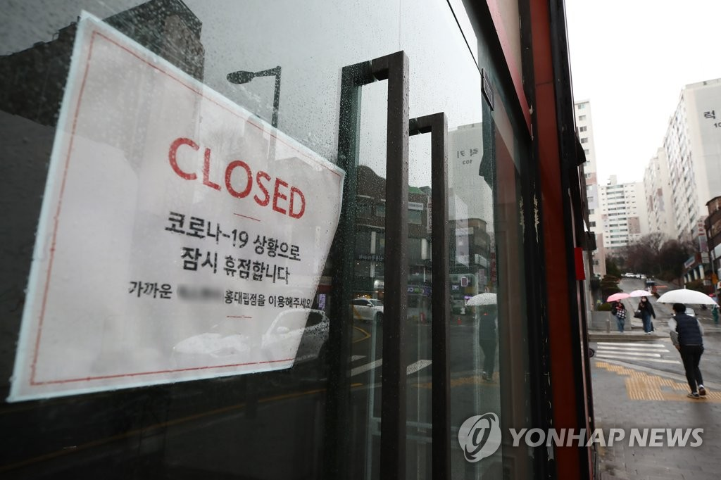 This photo, taken March 1, 2021, shows a sign announcing a temporary business closure due to the pandemic that was put up at a store in Seoul's college district in western Seoul. (Yonhap)