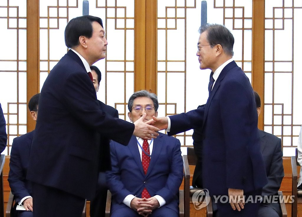 "This file photo, taken on July 25, 2019, shows President Moon Jae-in (R) shaking hands with Yoon Seok-yeol after conferring him a letter of appointment as prosecutor general. On March 4, 2021, Yoon offered to resign, and Moon accepted it. Yoon's surprise resignation came amid his confrontation with the ruling party over the latter's move to take investigative power away from the prosecution, which he criticized as a ""regression of democracy and destruction of the spirit of the Constitution."" (Yonhap)"