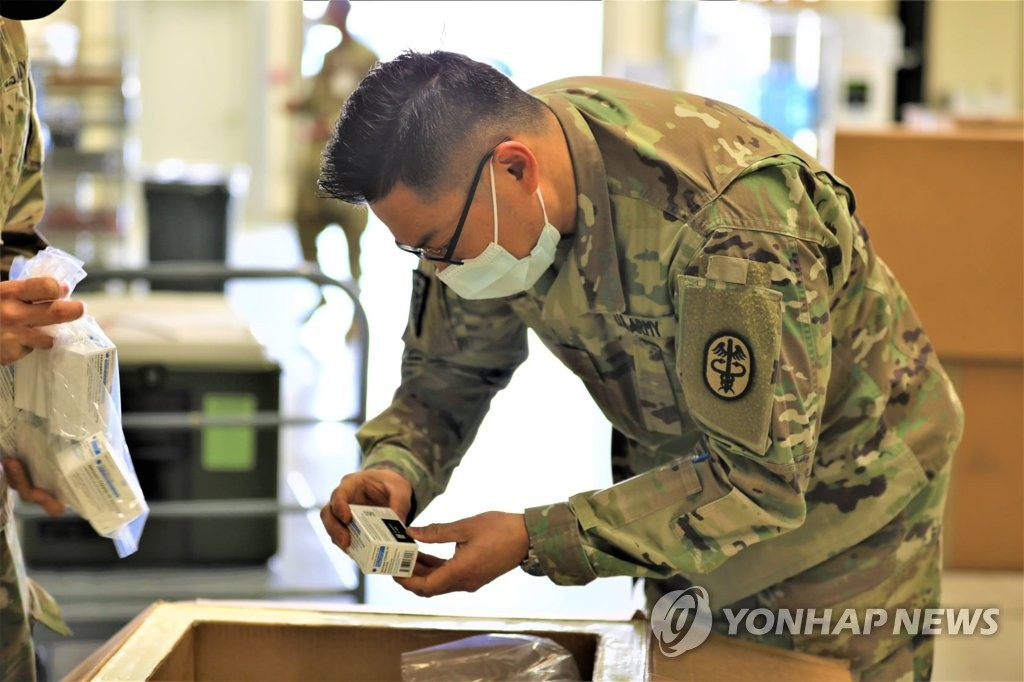 This file photo, captured from the Facebook account of the U.S. Forces Korea (USFK), shows an American medic looking at the first batch of Janssen COVID-19 vaccines that the USFK introduced on March 9, 2021, at Brian D. Allgood Army Community Hospital at Camp Humphreys in Pyeongtaek, 70 kilometers south of Seoul. (PHOTO NOT FOR SALE) (Yonhap)