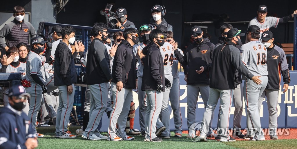 Hanwha Eagles players greet their teammates at the dugout after the completion of the bottom of the seventh inning of a Korea Baseball Organization preseason game against the Doosan Bears at Jamsil Baseball Stadium in Seoul on March 23, 2021. (Yonhap)