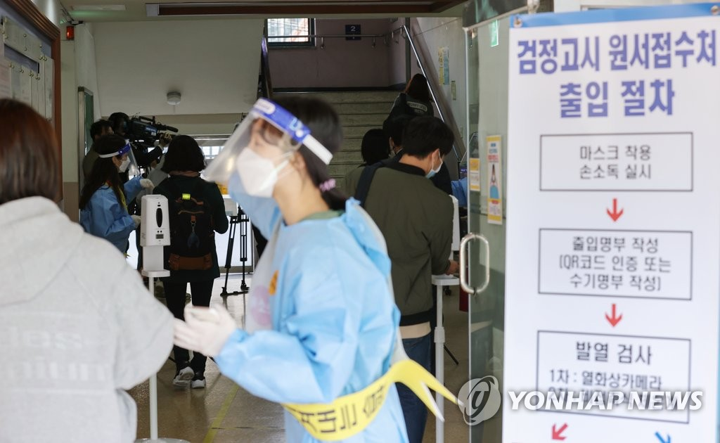 A health worker in a protective suit guides applicants for this year's school qualification examination at a middle school in Seoul on April 10, 2021. (Yonhap)