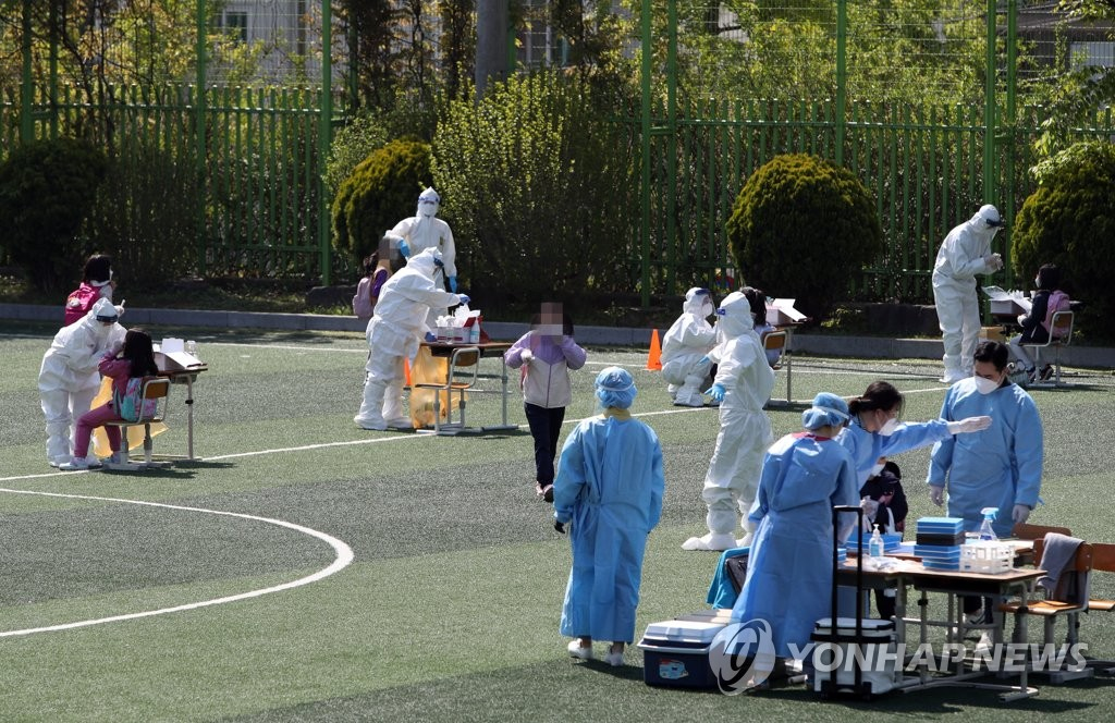 Health workers clad in protective suits collect samples from students and teachers at a makeshift virus testing clinic at an elementary school in Gwangju on April 19, 2021. (Yonhap)