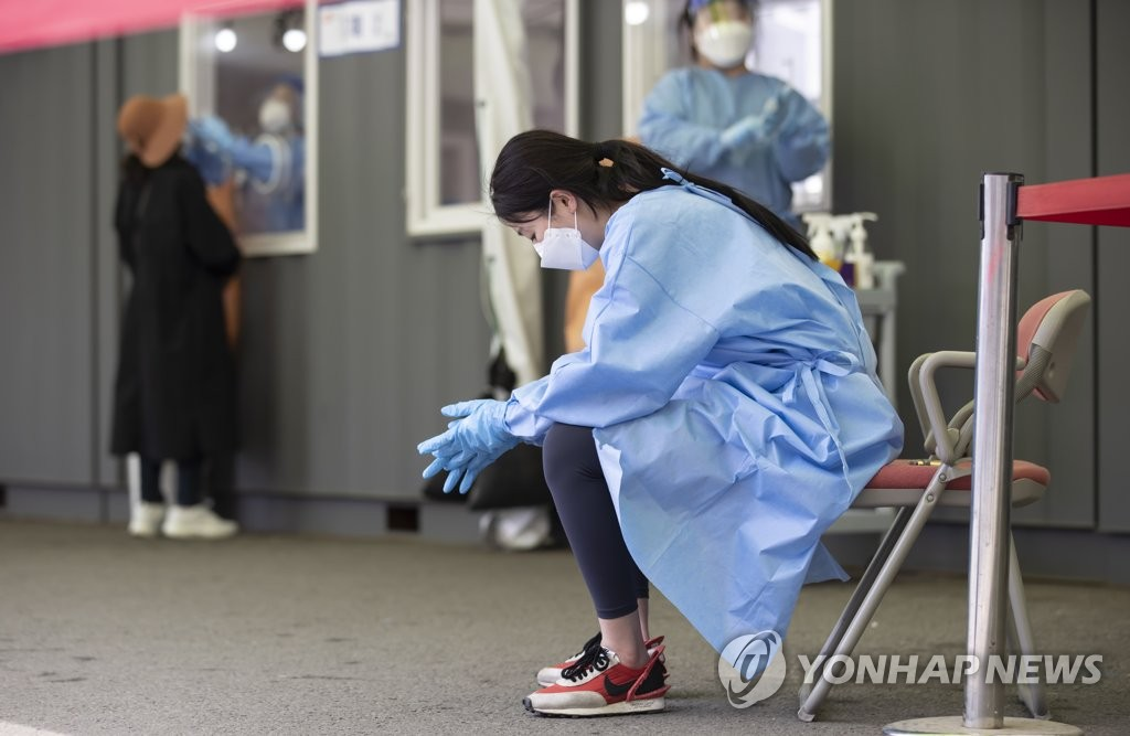 This photo taken on April 21, 2021, shows a health worker taking a rest at a makeshift virus testing clinic in Seoul. (Yonhap)