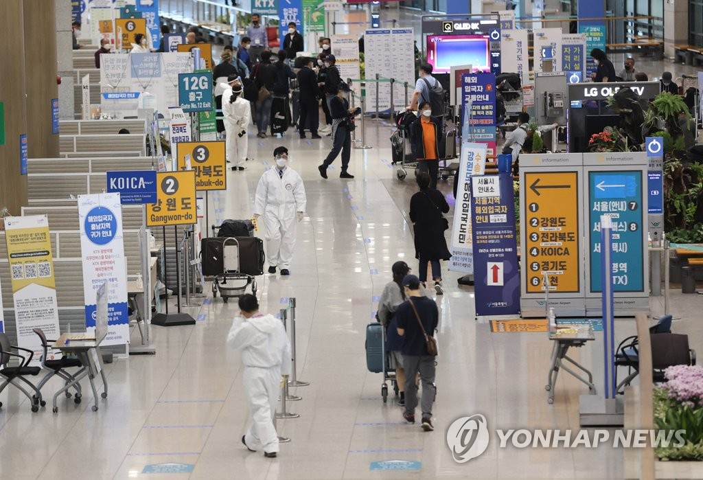 Health workers clad in protective suits guide arrivals at Incheon International Airport, west of Seoul, on April 22, 2021. (Yonhap)