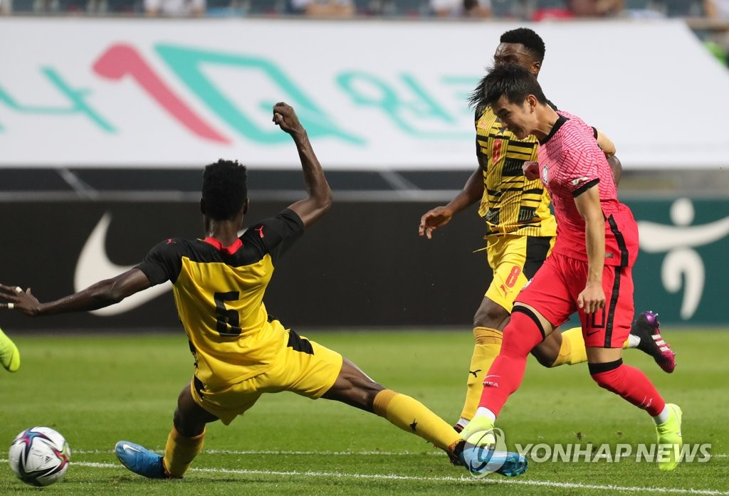 In this file photo from June 12, 2021, Kim Jin-gyu (R) of the South Korean men's Olympic football takes a shot against Ghana in a friendly match at Jeju World Cup Stadium in Seogwipo, Jeju Island. (Yonhap)