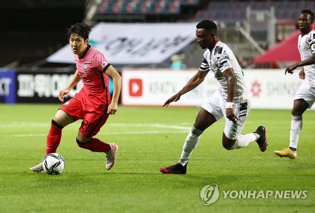 Lee Kang-in (L) of the South Korean men's Olympic football team dribbles past Sabit Abdulai of Ghana during a friendly match at Jeju World Cup Stadium in Seogwipo, Jeju Island, on June 15, 2021. (Yonhap)
