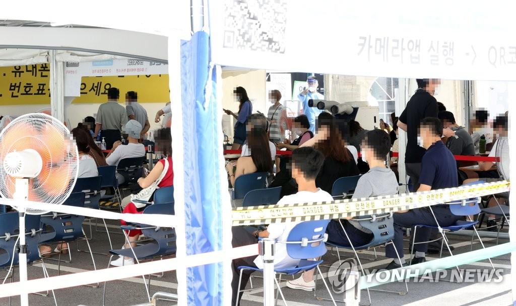 People wait to take coronavirus tests at a testing center in Gangnam, southern Seoul, on Aug. 16, 2021. (Yonhap)