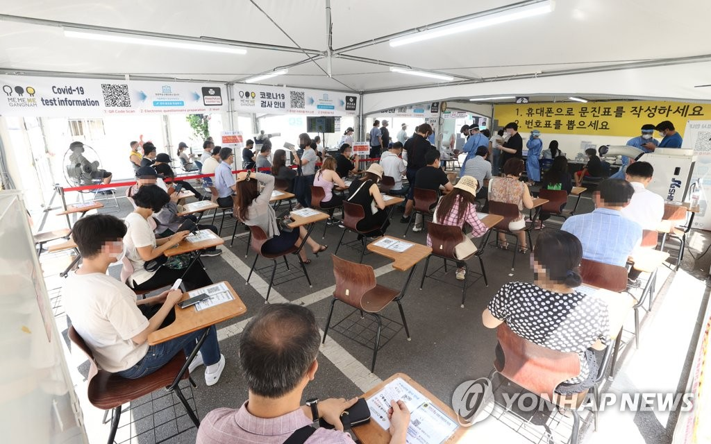 This photo taken on Aug. 17, 2021, shows people waiting to take a coronavirus test at a testing center in Gangnam, southern Seoul. (PHOTO NOT FOR SALE) (Yonhap)