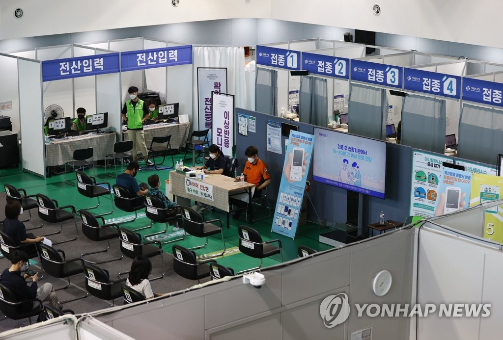 People wait to check for symptoms of possible side-effects from COVID-19 shots at a makeshift clinic at a gym in western Seoul on Sept. 3, 2021. (Yonhap)